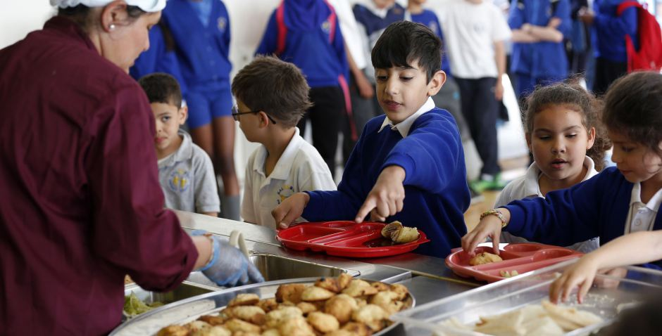 Students receive their lunch at Salusbury Primary School in northwest London